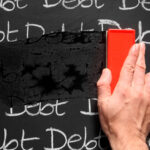 Erasing the word debt on a chalkboard